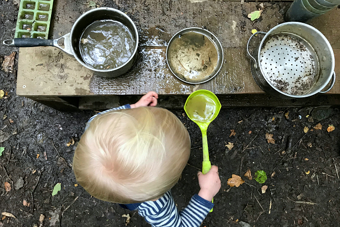 Otto at Forest School 23 months scooping water  transferring with ladel