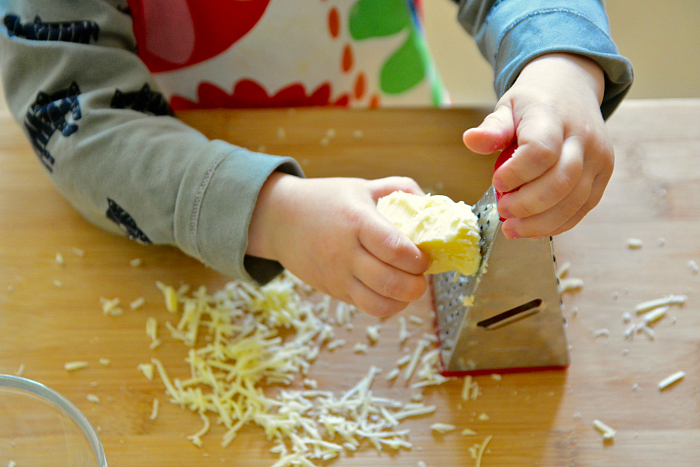 Montessori toddler grating cheese at 24 months at How we Montessori  #2