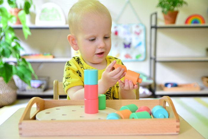Otto with wooden stacking pegs at How we Montessori   Lovevery toddler box