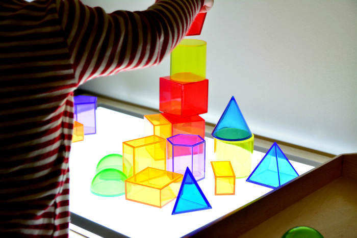Otto 20 months with shapes on light table at How we Montessori