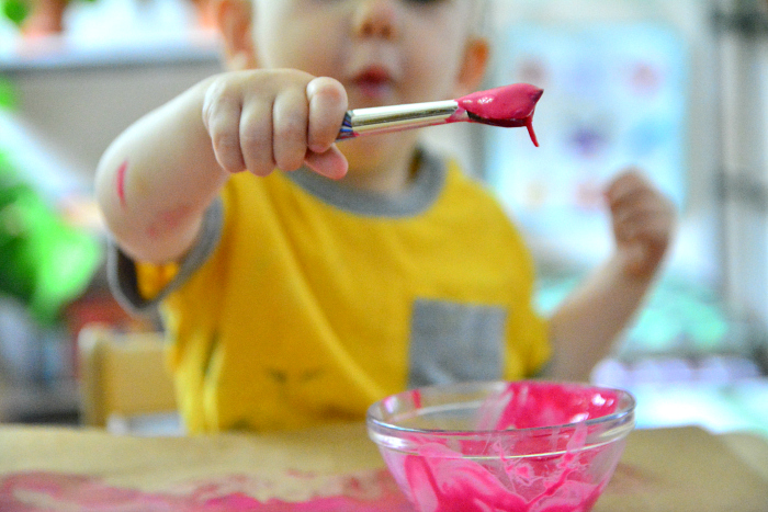 Otto scooping paint at How we Montessori 21 months