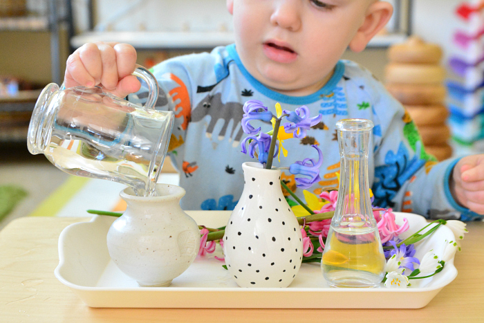 Otto pouring water at 18 months at How we Montessori toddler flower arranging