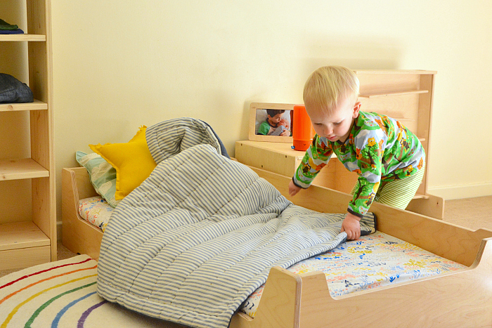 Otto making his bed at 23 months at How we Montessori