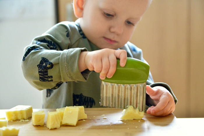 Montessori toddler wavy knife chopping cheese at 24 months Otto practical life