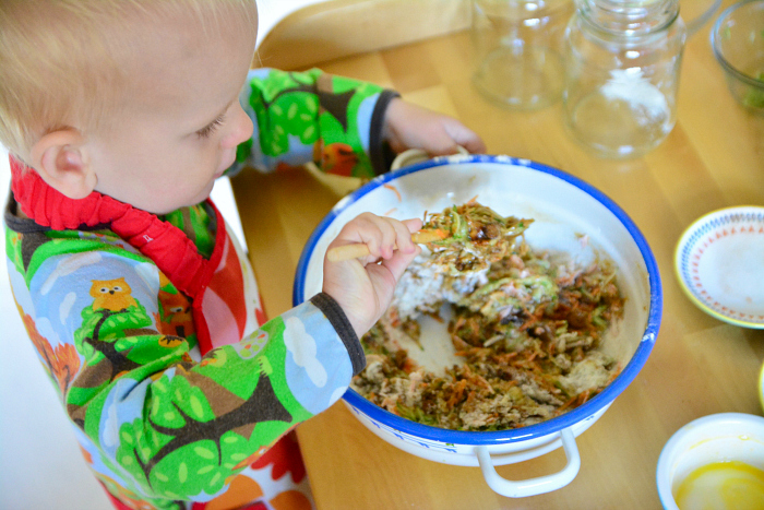 Montessori toddler baking carrot zucchini muffins at 24 months