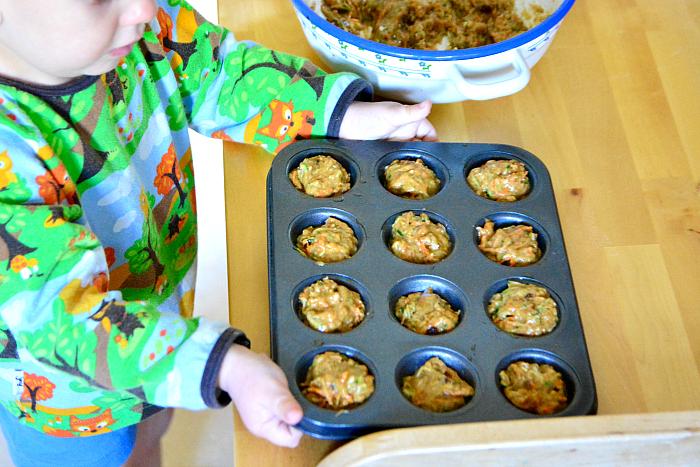 Montessori toddler baking carrot zucchini muffins at 24 months