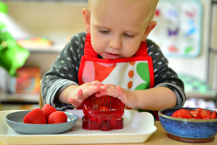Montessori toddler strawberry slicer at How we Montessori Otto 21 months