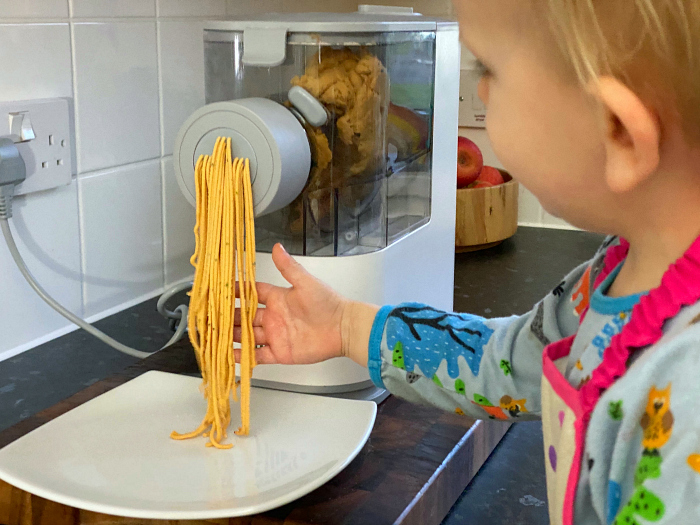 Toddler making spaghetti at How we Montessori home made pasta