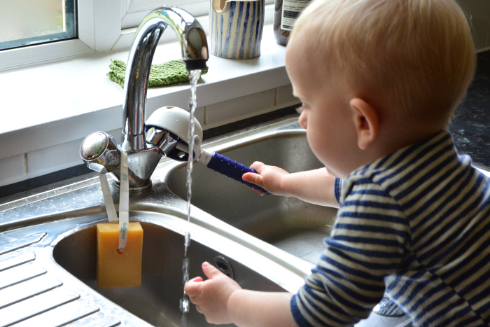 Montessori toddler using sink tap independently using tap extender tap turner at How we Montessori