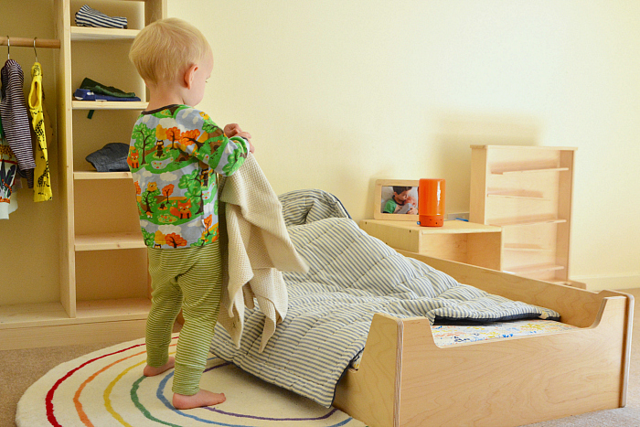 Otto making bed with blanket at How we Montessori  making bed at 23 months toddler chores