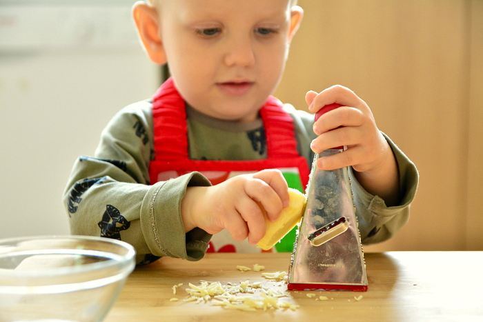Montessori toddler grating cheese at 24 months at How we Montessori