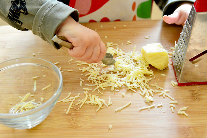 Montessori toddler using mini tongs to transfer cheese into bowl at How we Montessori