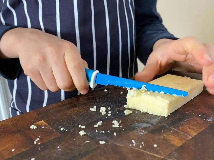 Otis at How we Montessori using the Kiddi Kutter knife on cheese