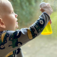 Montessori toddler with a mini spray bottle at how we montessori Otto at 27 months window washing practical life