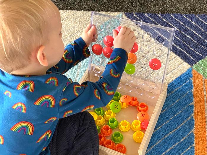 Otto  using Lovevery peg board at How we Montessori
