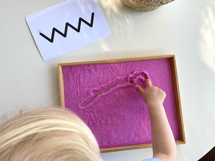 Montessori toddler prewriting fine motor skills using sand tray to draw people
