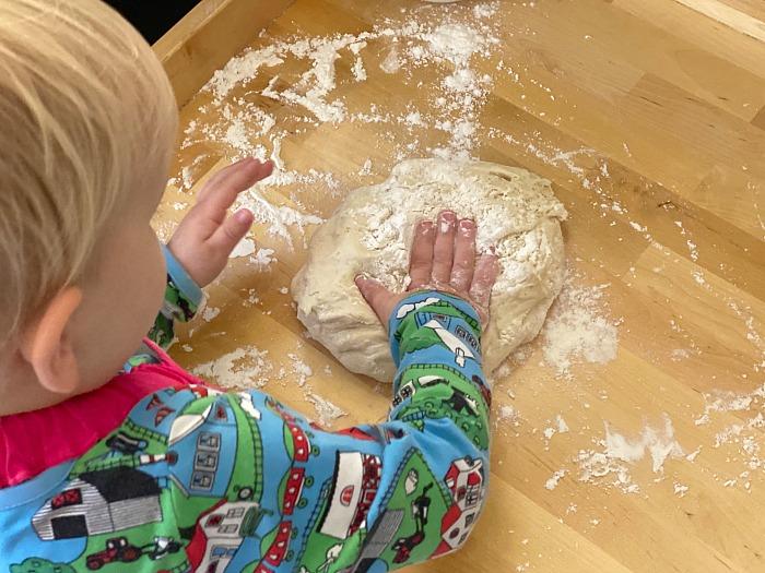 Montessori toddler making bread pouring water