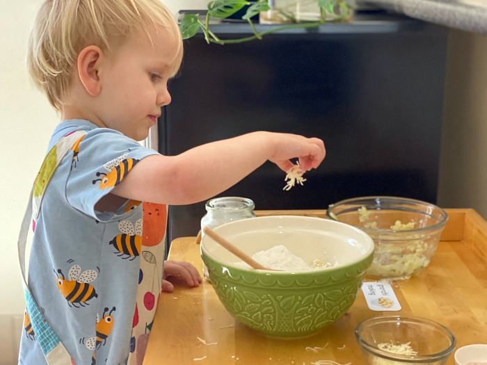 Otto adding cheese to gnocchi at How we Montessori