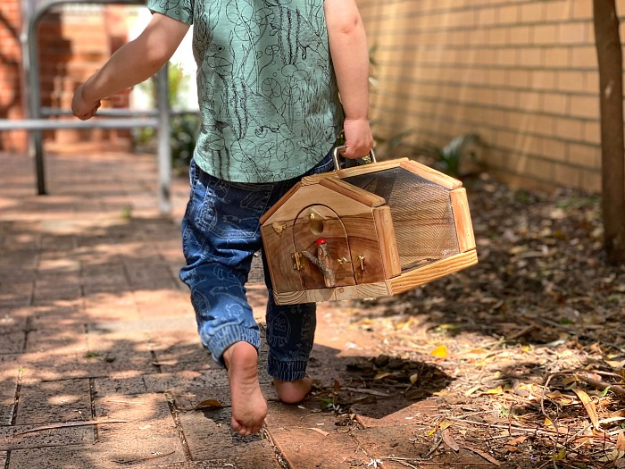 Otto walking with hand made wooden bug catcher at How we Montessori