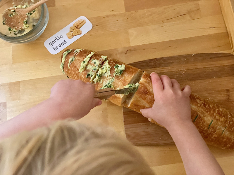 Spearding garlic bread practical life three year old cooking at How we Montessori