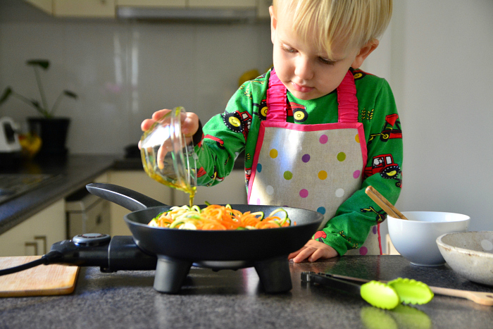 Toddler making noodles at How we Montessori cooking with electric skillet