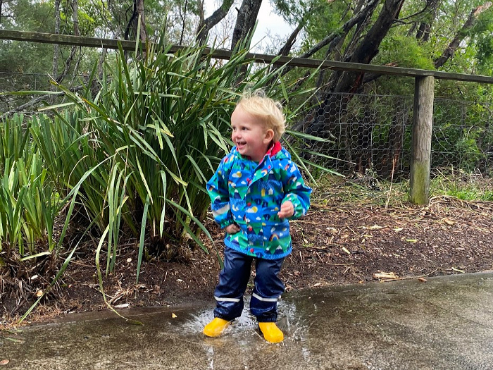 Jumping in puddles at How we Montessori nature walk in rain at two years