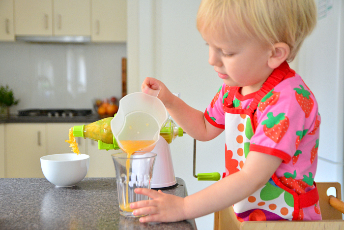 Toddler using hand crank juicer Montessori practical life at two years
