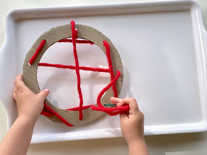Fine motor skills threading with wool tray at How we Montessori