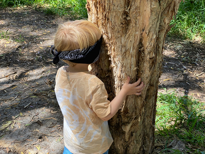 Forest School using blindfold to highten sense of touch at How we Montessori