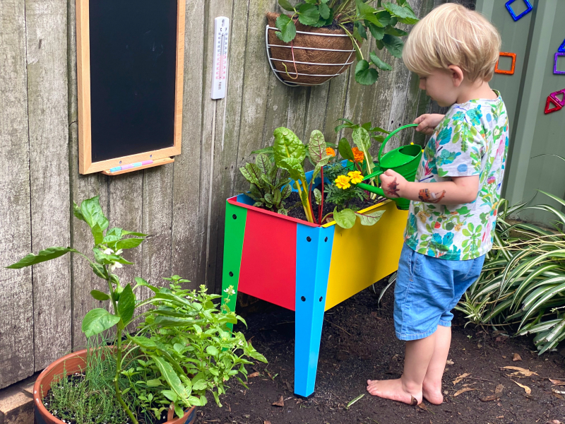 Otto watering raised garden bed at How we Montessori activity