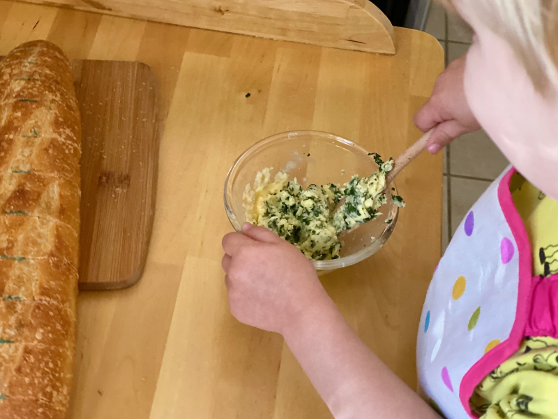 Mixing garlic butter at How we Montessori practical life activitiy three years old