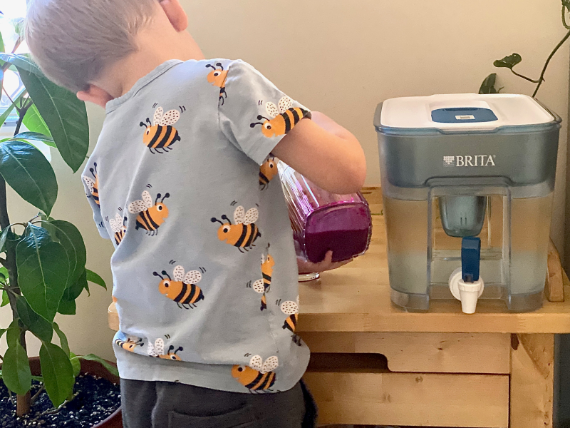 Otto pouring juice for breakfast at How we Montessori