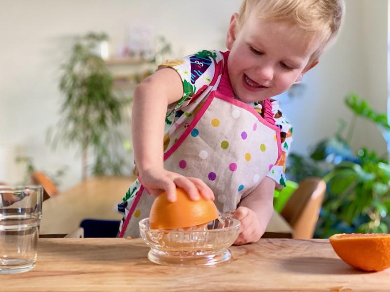 Juicing oranges at How we Montessori three year old