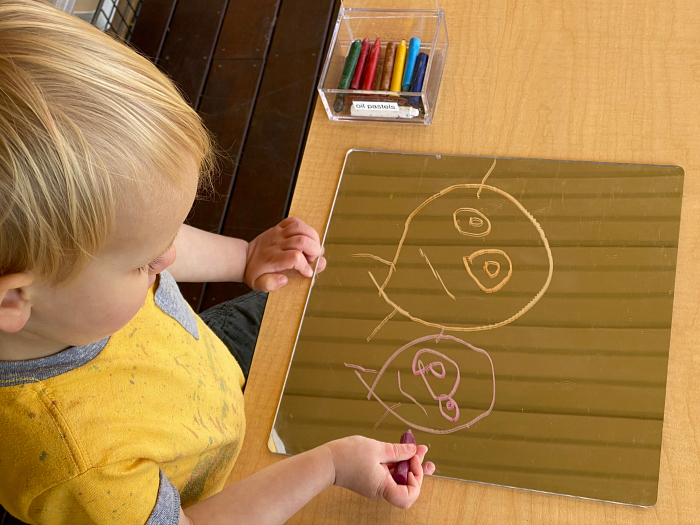 Oil pastels on mirror drawing mark making at How we Montessori toddler sydney
