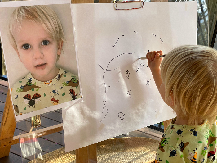 Otto drawing on easel at How we Montessori 2 years 11 months  footprints