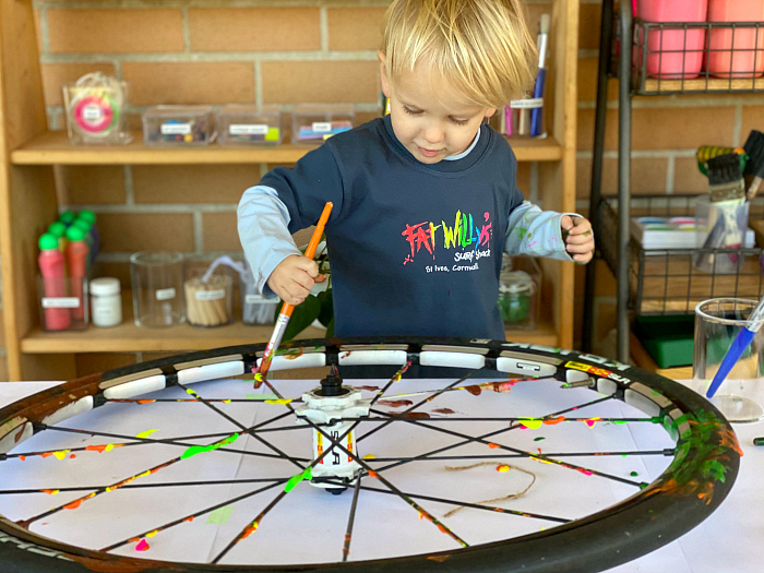 Otto painting bike wheel at How we Montessori
