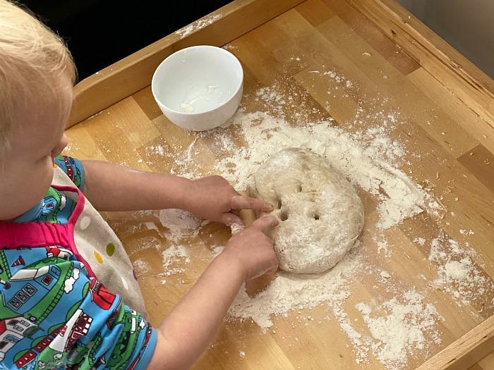 Otto poking bread at How we Montessori