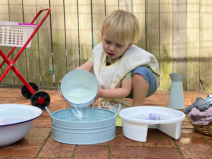 Montessori toddler washing pouring water from bucket