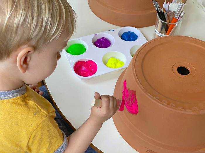 Painting planter with paintbrush at How we Montessori