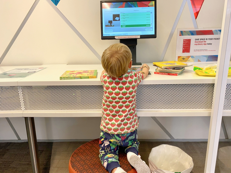Otto checking out books at the library at How we Montessori three years old library love