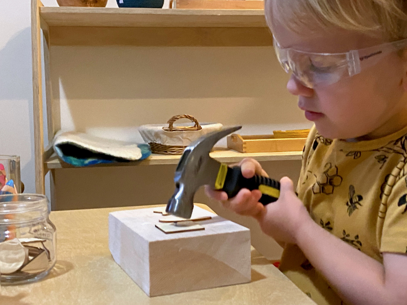 Otto hammering three years old preschool at How we Montessori woodworking