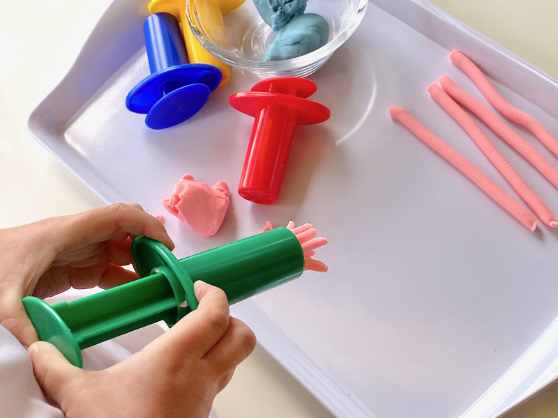 Play dough extruder tray to rotate activity at How we Montessori