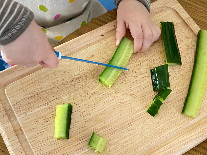 Otto cutting cucumber at How we Montessori toddler