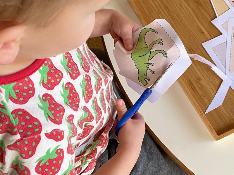 *cutting at three year old dinosaur shapes at How we Montessori