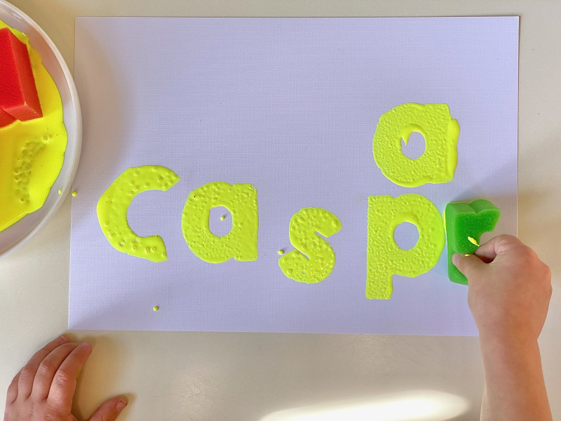 Alphabet paint stampers at How we Montessori learning to write spell name