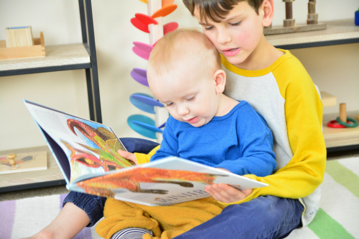 Reading with siblings and friends at How we Montessori