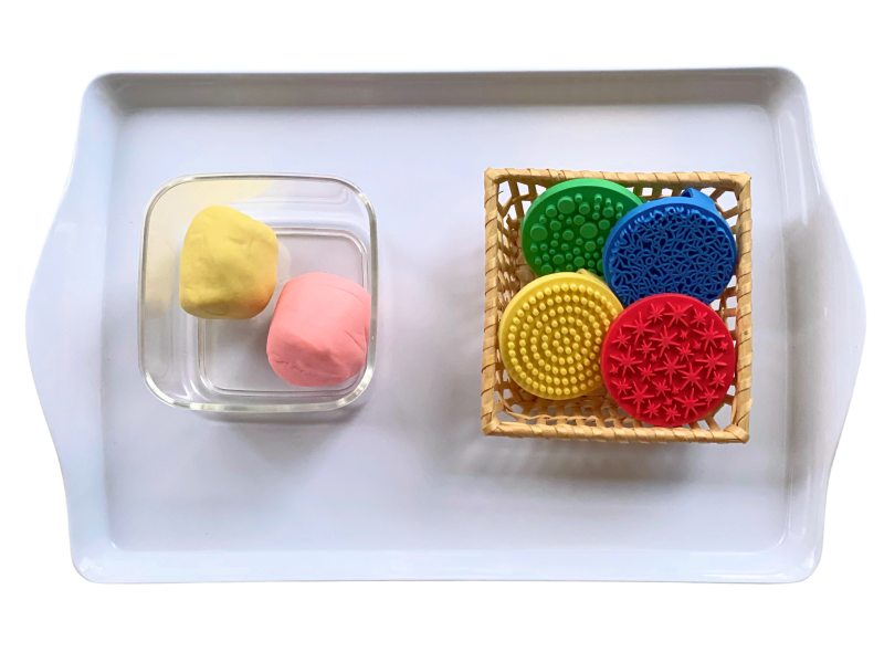Play dough textured stampers at How we Montessori play dough tray to rotate