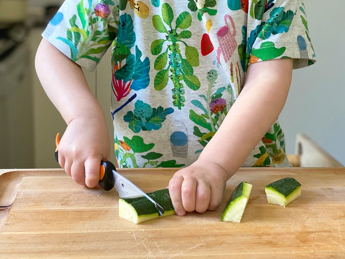 Montessori toddler chopping with wavy knife crinkle cutter at How we Montessori Otto at 24 months