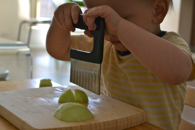 Cutting apple at 18 months with crinkle cutter  with handle at How we Montessori