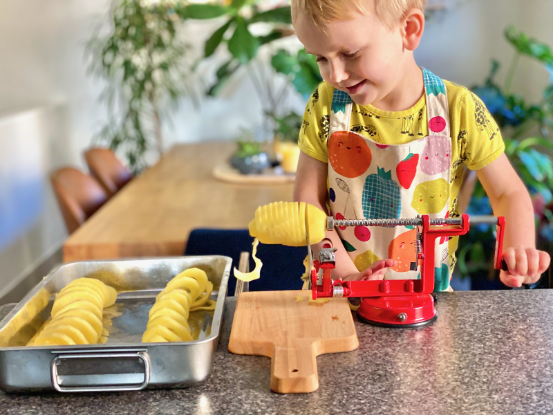 Sprinkling dried herbs at How we Montessori three year old food preparation snack